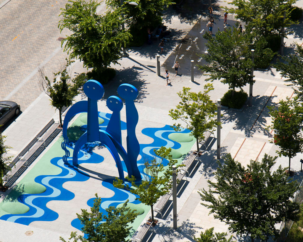 Aerial view of art installation of giant blue people on Front street Canary District