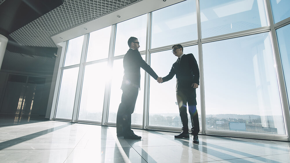 Two men shaking hands at top of a skyscaper with sun shining through the windows.