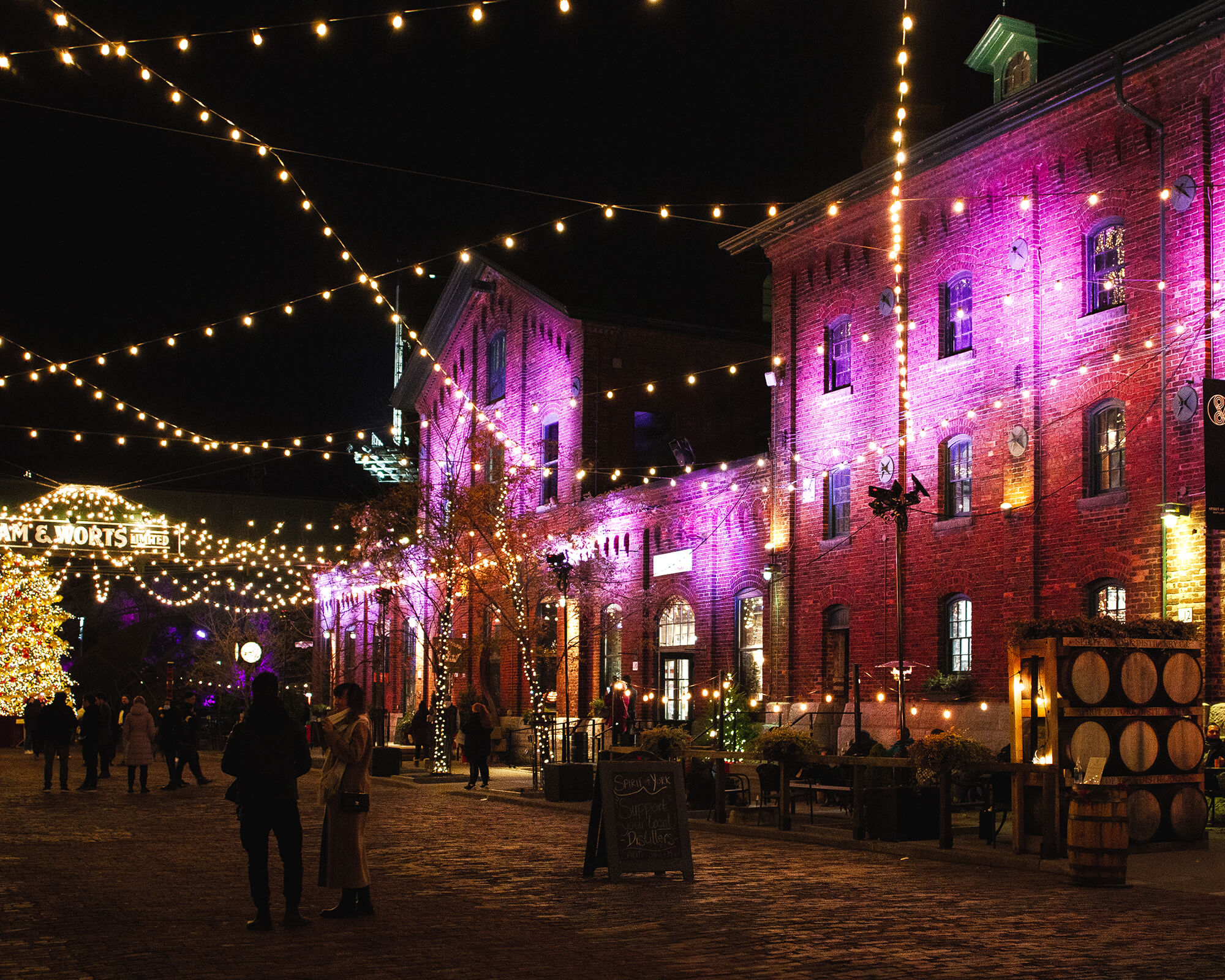 Nighttime image of the distillery district's 2020 Winter Village celebration with Christmas lights hanging over the space and people walking by