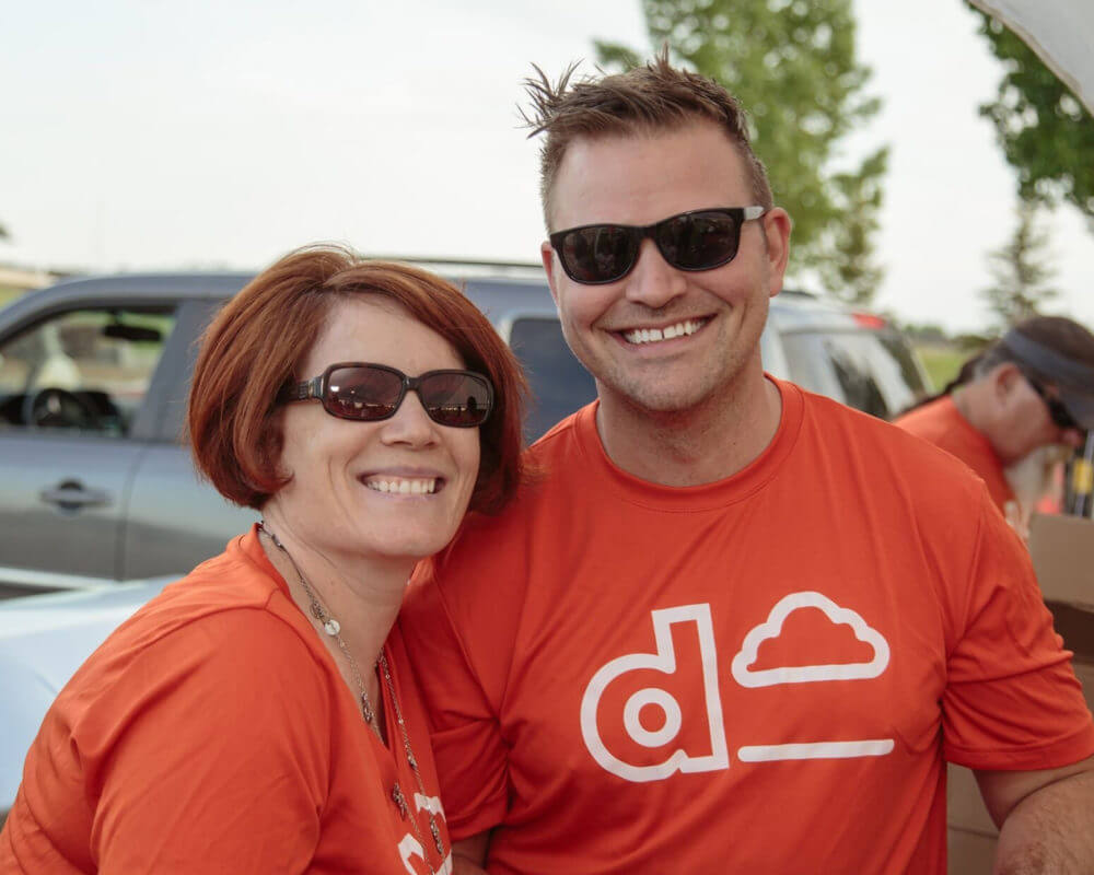 Two Dream Employees wearing orange shirts with the Dream logo smiling while volunteering at a charity organization.