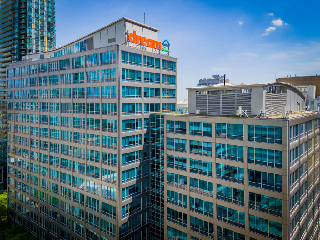 Blue skies drone shot of Dream's 30 Adelaide Street East office with the orange Dream logo on the rooftop.